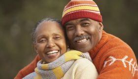 Middle-aged African American couple hugging outdoors
