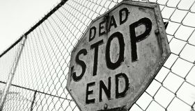 'Stop, Dead End' sign on chain link fence (B&W)