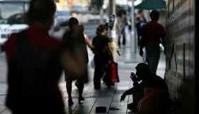 Pedestrians walk past a homeless man begging in the underpass street near Parama