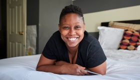 Smiling Black woman laying on bed holding cell phone