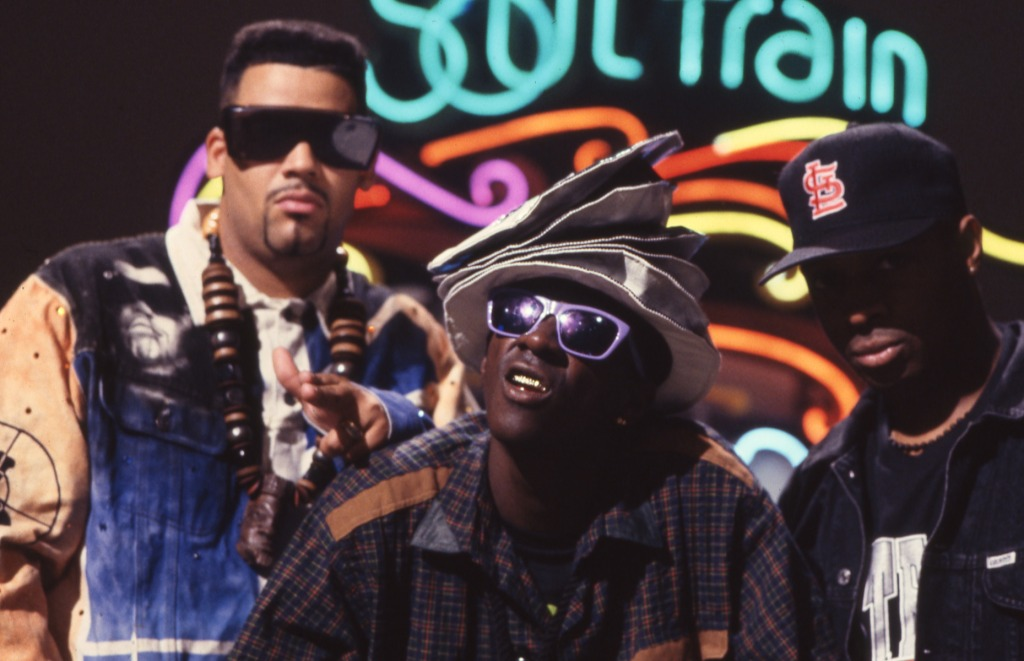Hip Hop group Public Enemy stand in front of the neon Soul Train sign.