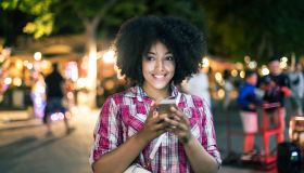 Smiling woman using smart phone on street at night