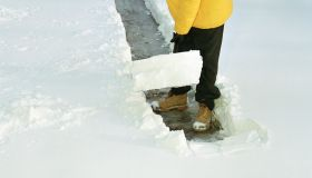 Teenage boy (16-18) shoveling path through snow, elevated view