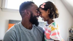 Father and daughter laughing in bedroom - stock photo